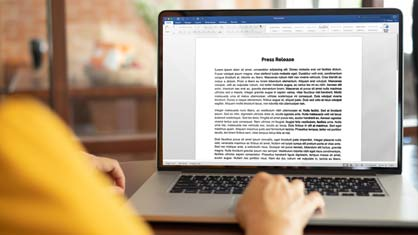 Woman creating a template for a press release using Microsoft word