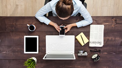 Woman sitting at a desk using her phone and laptop